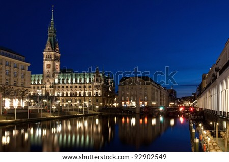 Hamburg Rathaus (city hall) at night with the Small Alster and the Alster arcades.