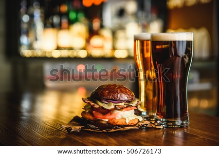 Hamburger and dark light beer on a pub background.