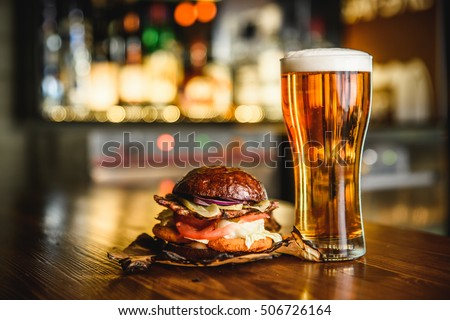 Hamburger and light beer on a pub background.