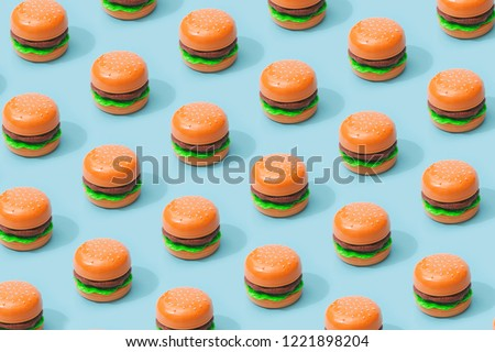 Hamburger fast food pattern on pastel blue background. Minimal junk food concept.