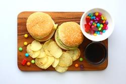 Hamburger, fried potato, candy, coke on wooden plate