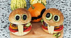Hamburger in the form of a funny monster with eyes and tongue on a light wooden board. Menu for Halloween.