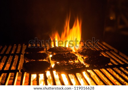 Hamburger patties grilling with charcoal barbeque flames