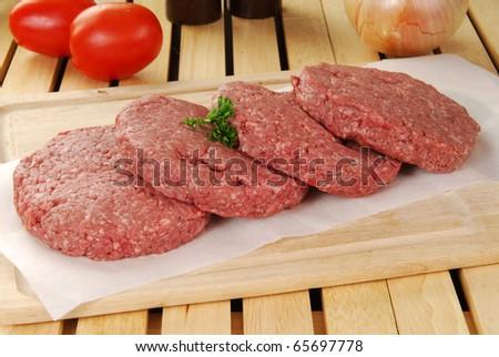 Hamburger patties on a chopping board