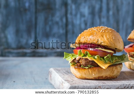 Hamburger with beef, cheese and vegetables on rustic table. Closeup with copy space