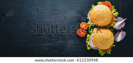 Hamburger with cheese, meat, tomatoes and onions and herbs. On Wooden background. Top view. Free space.