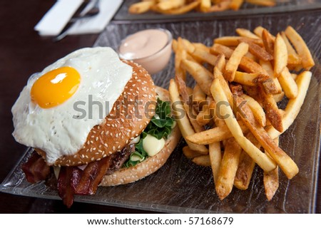 hamburger with fried egg on top and fries