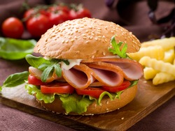 Hamburger with ham, tomato and lettuce, selective focus