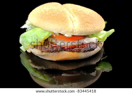 Hamburger with lettuce, tomato and onion isolated on black