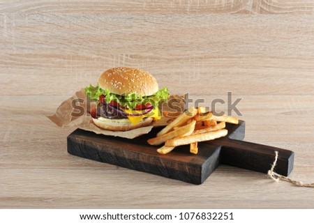 Hamburger with minced beef patties with tomato, salad, bacon, cheese, sauce and onions. Next to the hamburger is French fries. Close-up. Light background.
