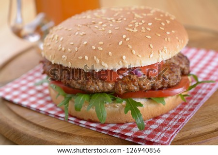 Hamburger with tomato and arugula and beer