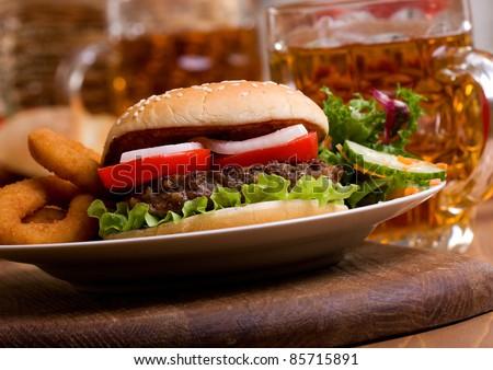 hamburger with vegetables and mug of beer