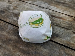 Hamburger wrapped on label white paper on wooden table.