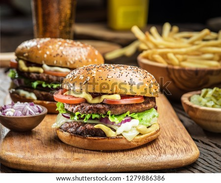 Hamburgers and French fries on the wooden tray.