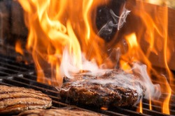 hamburgers cooking hamburgers on grill with flames. beef steak on the grill with flames. barbecue burgers for hamburger prepared grilled on bbq fire flame grill