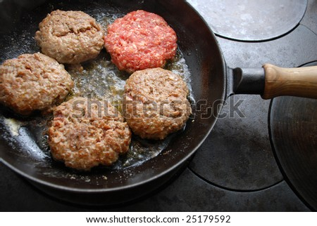 Hamburgers in a frying pan one raw