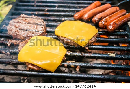 hamburgers with cheese and hot dogs on grille on camping trip