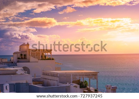 Hammamet, Tunisia. Image of architecture of old medina with dramatic sky at sunset time. #727937245