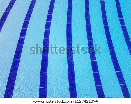 HAMMAMET, TUNISIA - JUNE 19, 2018: Blue lines of a swimming pool. Hammamet is a popular destination for its beaches, swimming and water sports #1129421894