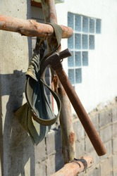 Hammer and a waist belt pocket for the device, hanging on wooden stairs.
