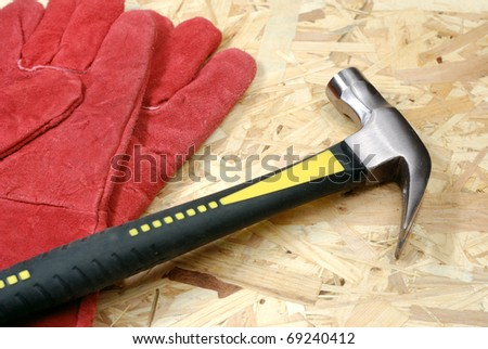 Hammer and gloves over plywood