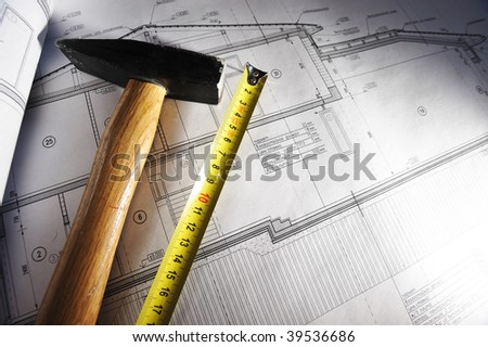 Hammer and measure tape over house plan blue prints