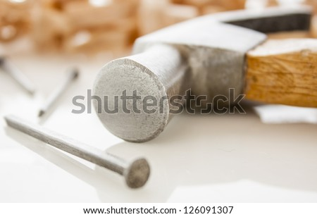 hammer and nails on a wood board with sawdust shavings