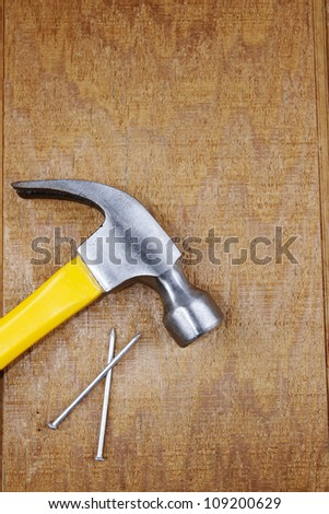 Hammer and nails on wooden panel