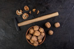 Hammer and walnut in a bowl against the concrete