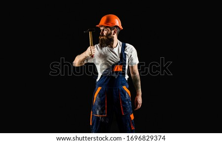 Hammer hammering. Builder in helmet, hammer, handyman, builders in hardhat. Copy space. Bearded builder isolated on black background. Bearded man worker with beard, building helmet, hard hat.