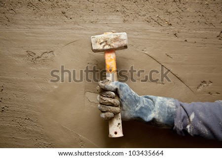 hammer man hand with gloves in grunge cement mortar background