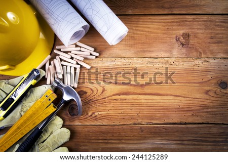 hammer, protective gloves, folding ruler, model knife, blueprint, wooden dowels  and yellow safety helmet on wooden background
