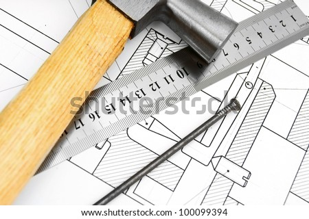 Hammer, ruler and nail on the drawing.