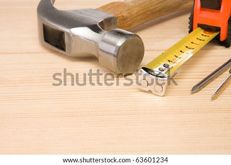 hammer, tape measure and nail on wood brick