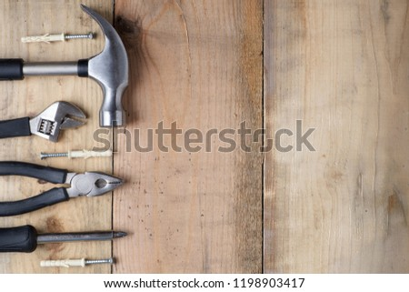 Hammer, wrench, screwdriver and pliers on a workbench, top view #1198903417