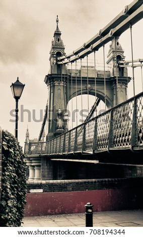 Hammersmith Bridge is a suspension bridge that crosses the River Thames in west London UK. This Picture Has a Vintage look. #708194344