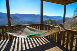 Hammock at terrace in the cabin. Cabin vacations. Hammock with view of blue mountains and blue sky at autumn sunny day. Rest and relax in a house in the mountains, Blue Ridge, GA, USA. Cabin getaway.