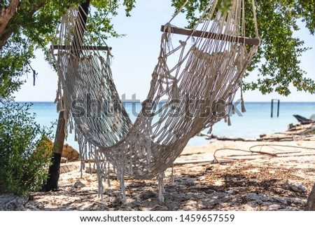 Hammock knitted from rough ropes on the beach. Hammock against blue sky and turquoise sea water. Rest, relaxation, peace.