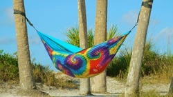 Hammock of rainbow colors hanging between the palm trees on beach. People on summer vacation relaxing in hammock.