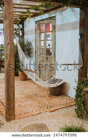 hammock on terrace with brick floor and pebble ground  under lathing shade in the garden mediterranean style. #1474797098