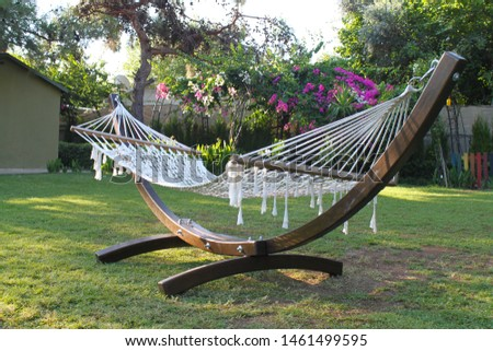 Hammock swing on natural background of green trees and grass. The concept of rest and relaxation #1461499595