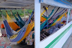 Hammocks on passengers deck on cattle pontoon boat on Rio Paraguay river, Corumba, Pantanal, Mato Grosso, Brazil, South America. These pontoons are floating from Corumba to Porto Jofre.