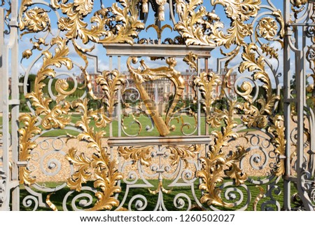 Hampton Court Palace exterior gold wrought iron gates designed by Jean Tijou in the 18th century and depicting a harp representing Ireland in the Union (at the time)