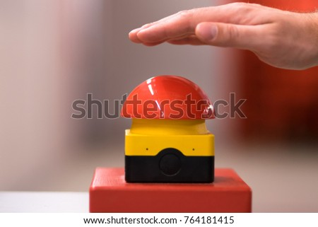 Hand above a red emergency button #764181415