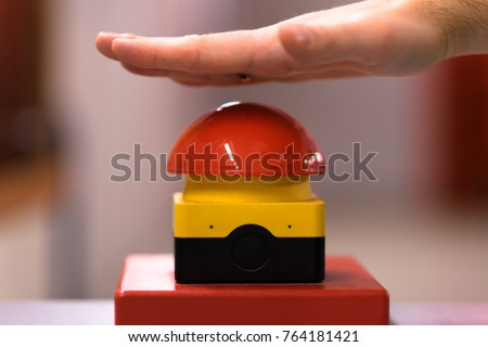 Hand above a red emergency button