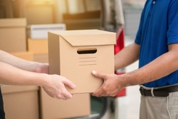 Hand accepting a delivery of boxes parcel cardboard from deliveryman. Messenger and delivery concept.