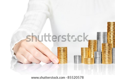 Hand adding a stack of coins to savings