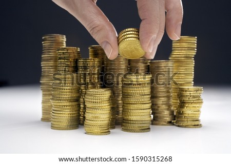 Hand adding money to stacks of assorted Euro coins