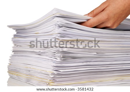 Hand adding more files to a large stack of documents - stock photo