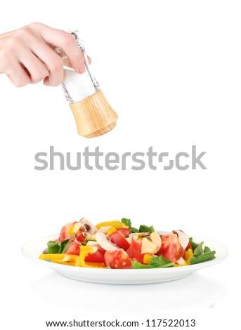 Hand adding salt using  salt shaker isolated on white - stock photo